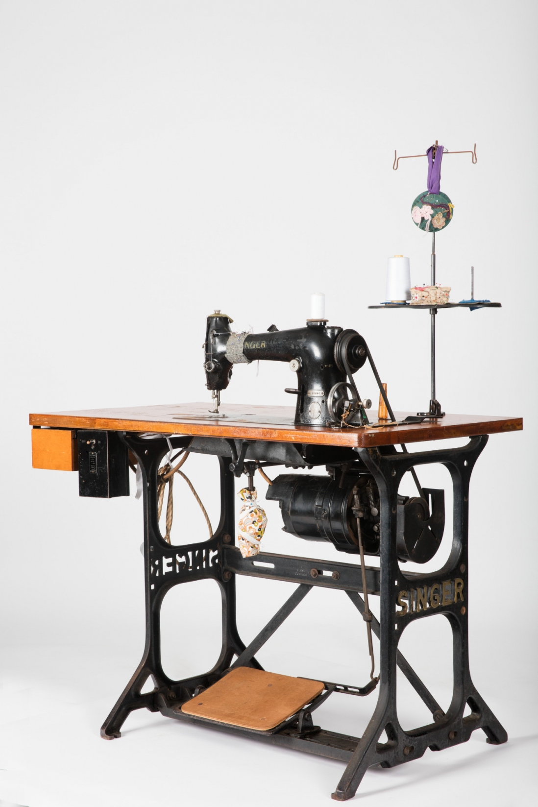 Metal framed sewing machine table with machine embedded.