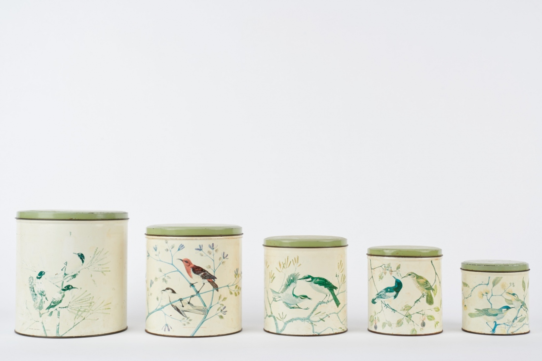 Five white canisters in descending size from left to right.