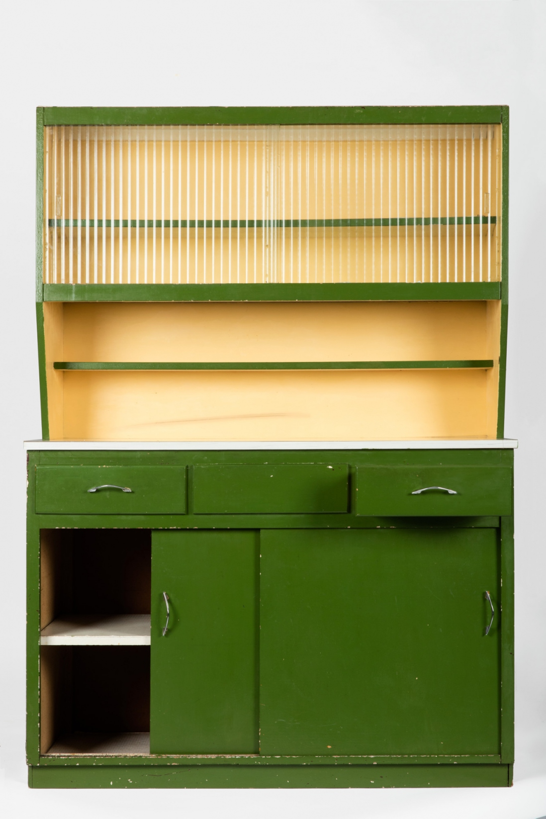 Green drawers with cream shelving above.