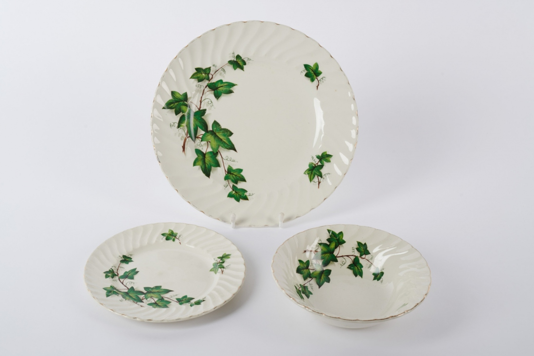 Three pieces of white crockery with green leaf design.