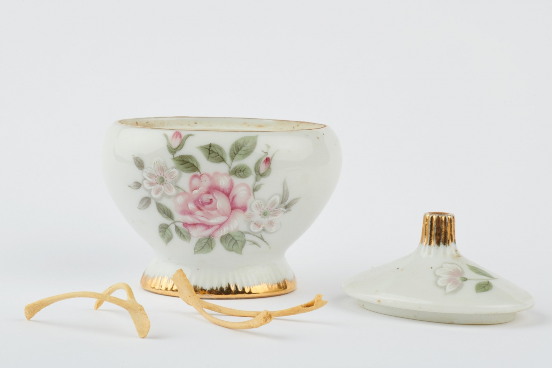 White dish with floral pattern, lid off and chicken bones next to it.