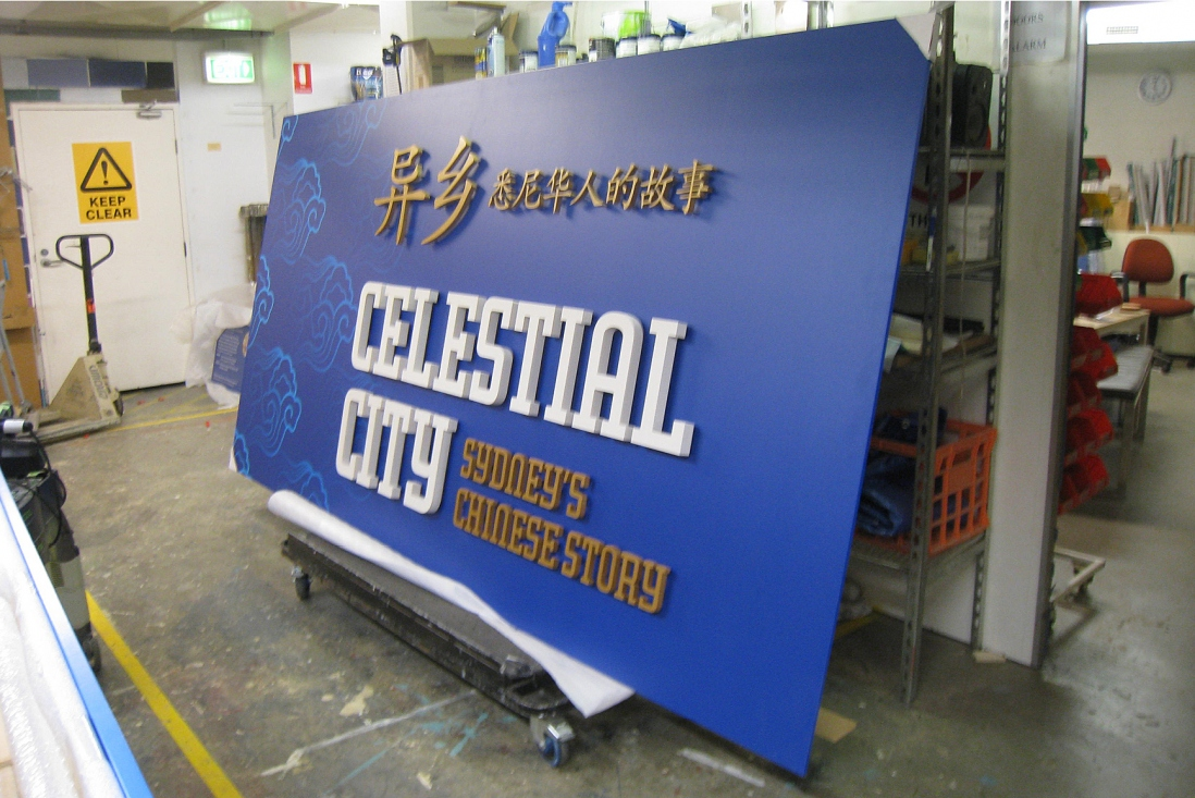 This is a photograph of a large blue wooden sign with gold and white lettering leaning vertically on a trolley