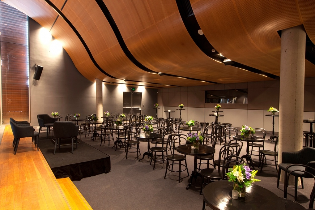 Large room with curved roof set up for cocktail function.