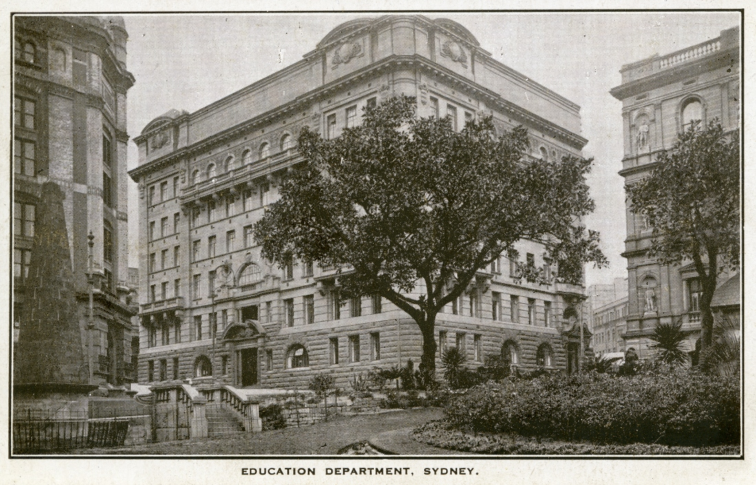 Black and white photo of large sandstone building on corner with tree in foreground.