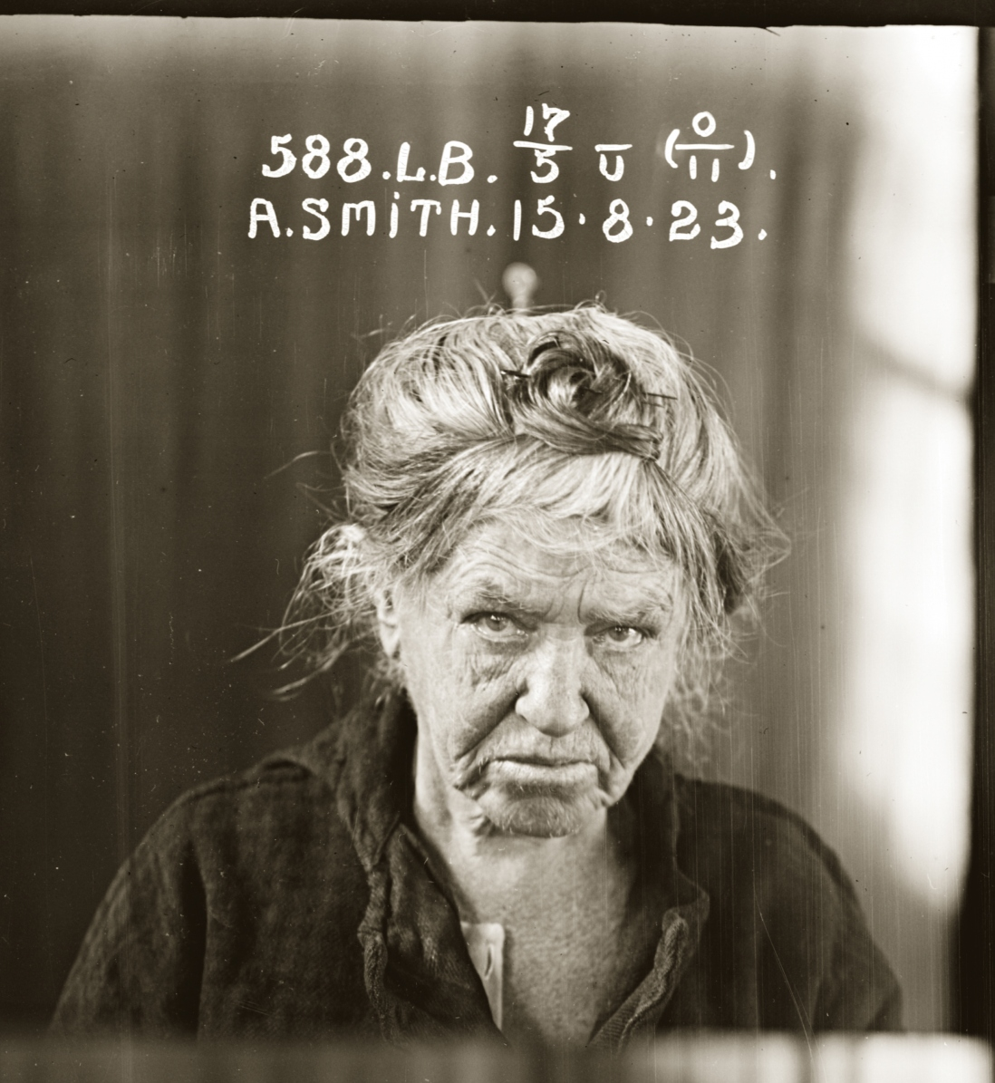 Black and white photo of older woman with white hair piled up on head, looking downcast. Image hand-inscribed with woman's details and date.