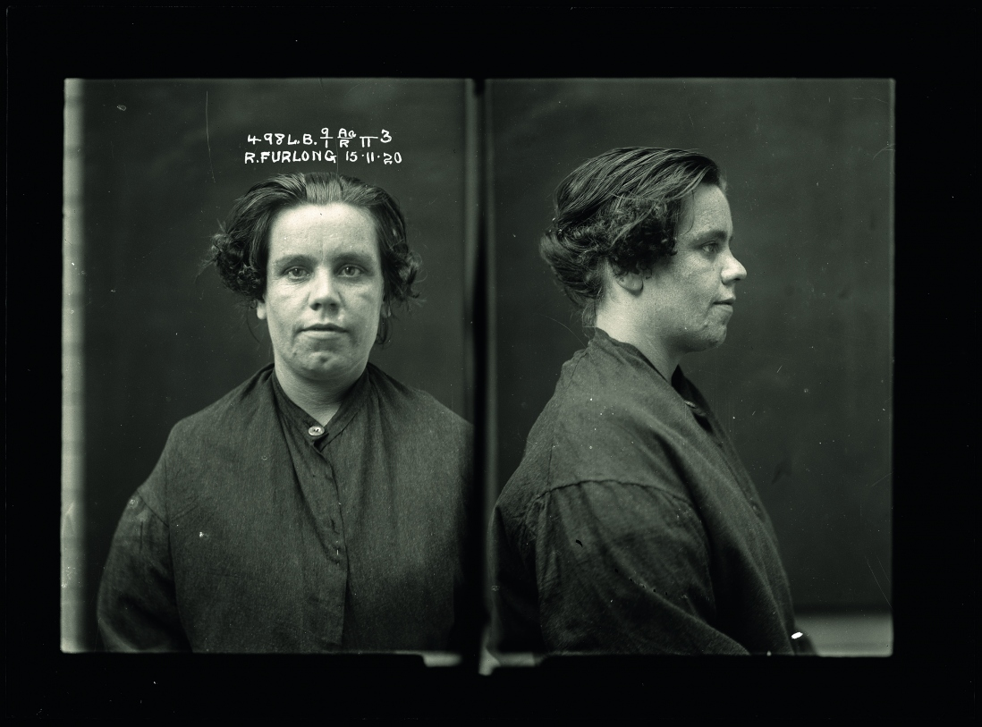 Police photograph of lady showing front and side of her torso. She wears a dark smock.