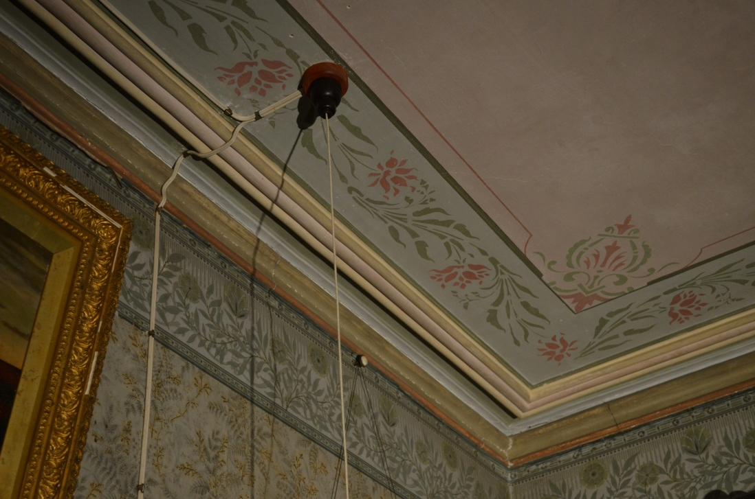 Detail of ceiling showing wiring added to wall and ceiling over existing wallpaper and cornices, leading to light switch with long hanging cord.
