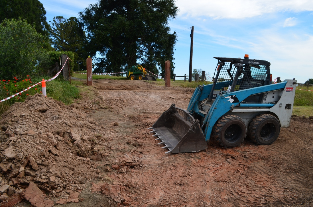 Blue excavator parked on partially excavated driveway.
