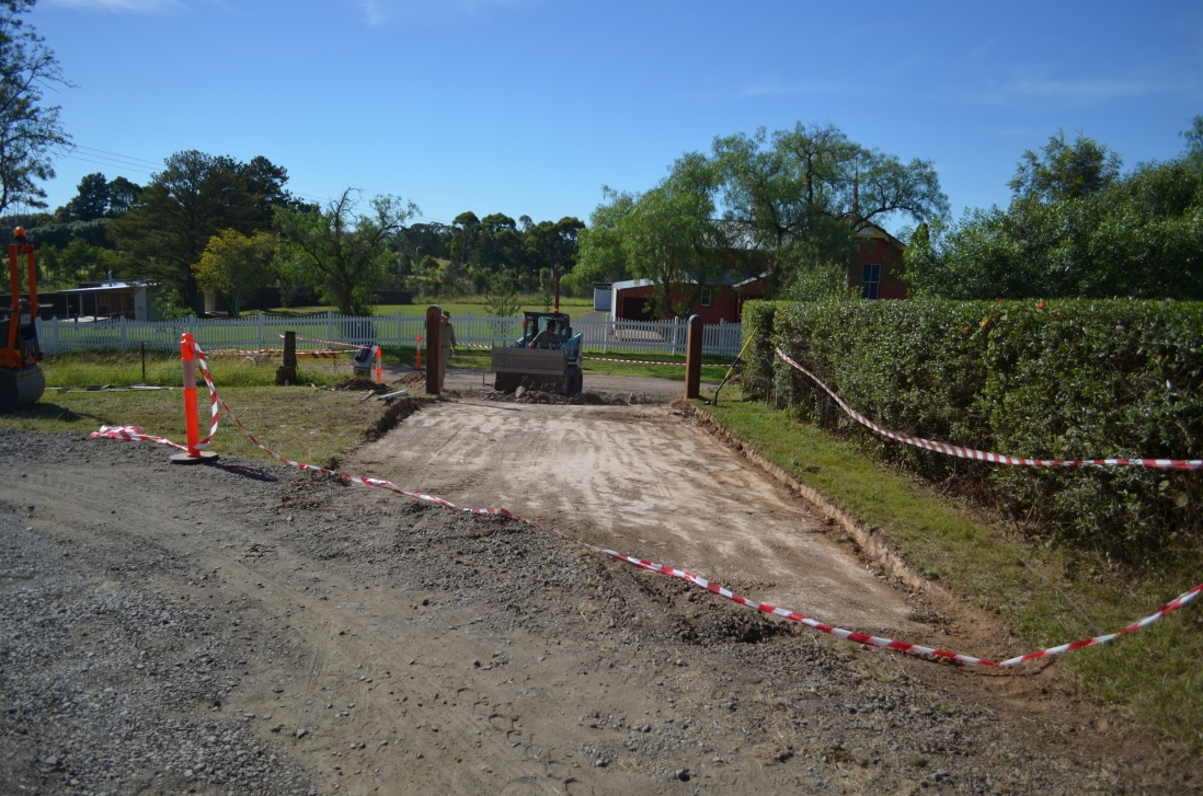 View down partially graded gravel drive towards new gate posts, with grader and school house in background.