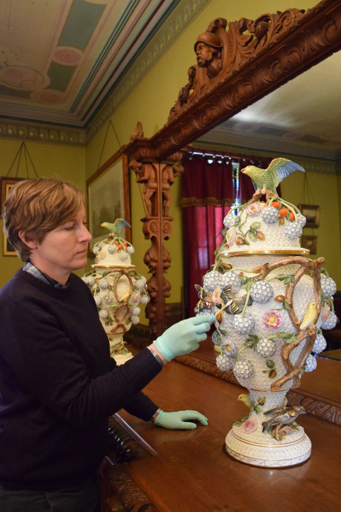 Person wearing gloves, cleaning large vase.