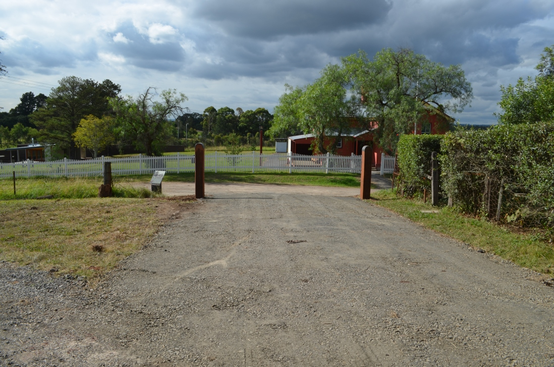 View down newly graded gravel drive towards new gate posts, with school house in background.