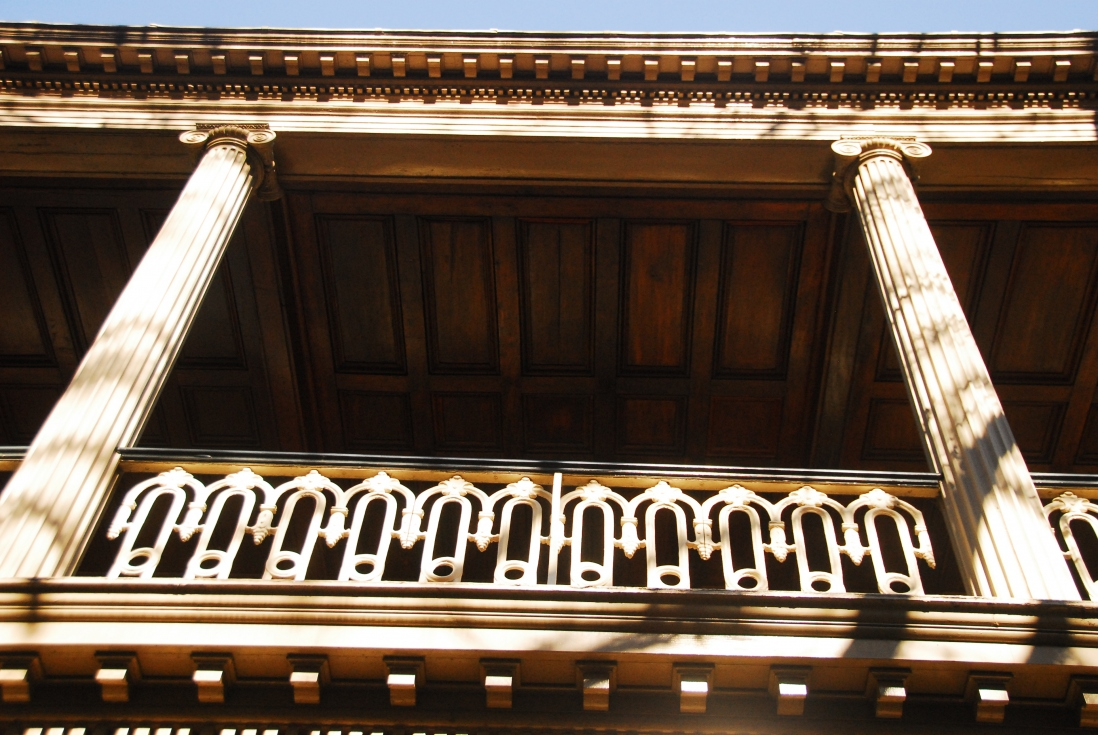 Looking up at darkened verandah, with columns, ironwork and two columns highlighted by sunlight.