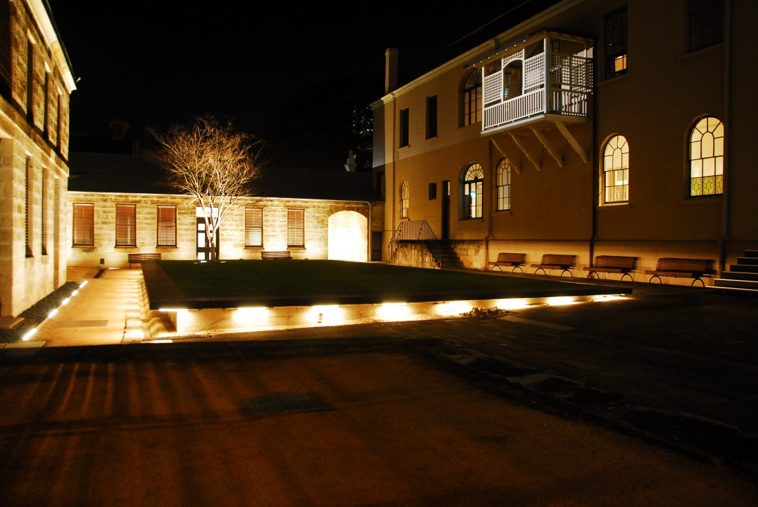 Night time lighting of the Mint buildings, showing back of the Rum Hospital building.