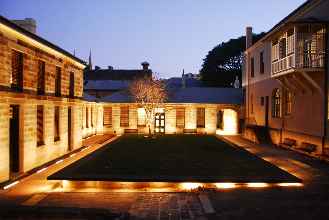 Night time lighting, looking across courtyard, bounded on three sides by buildings.