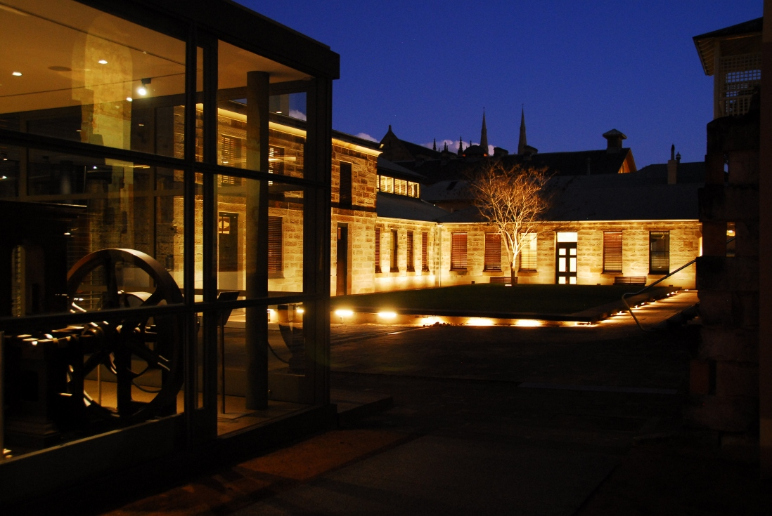 Night time lighting of the Mint buildings with glassfronted bar area to left and illuminated sandstone buildings in background.