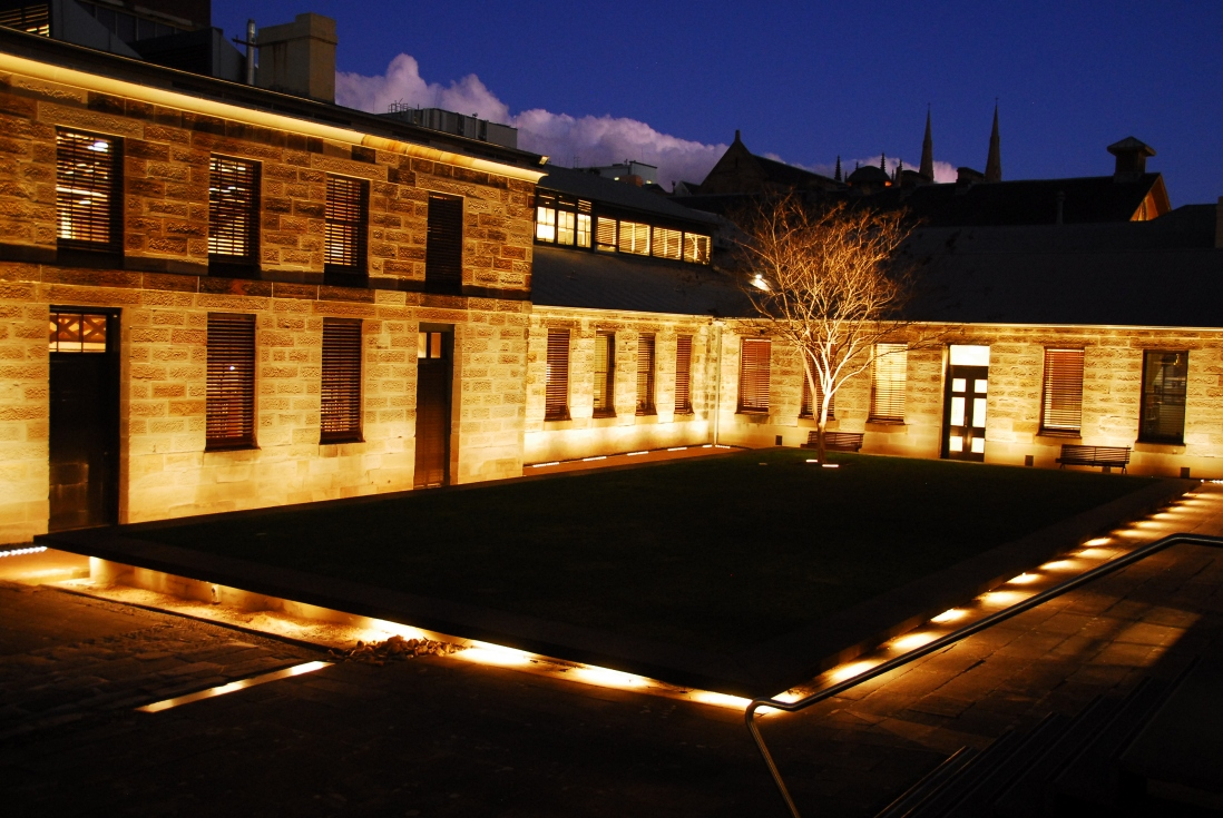 Night time lighting of the Mint buildings and courtyard.