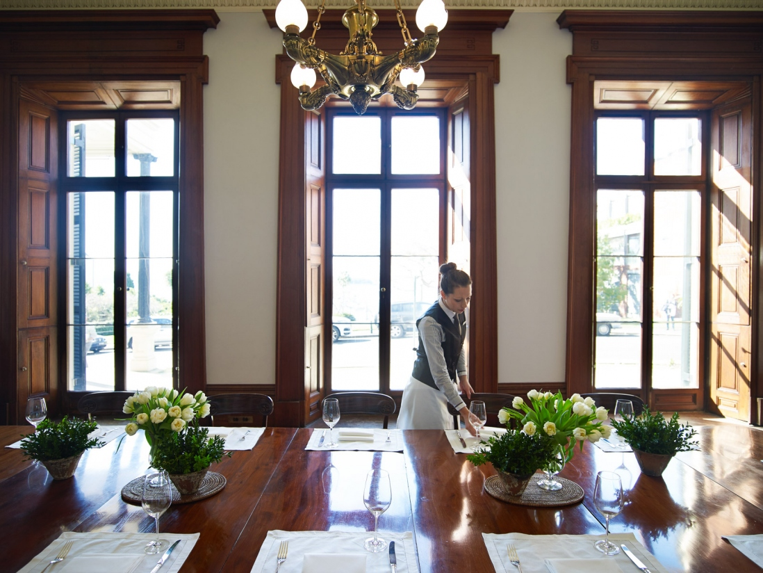 Woman setting up event in room with tall windows in background.
