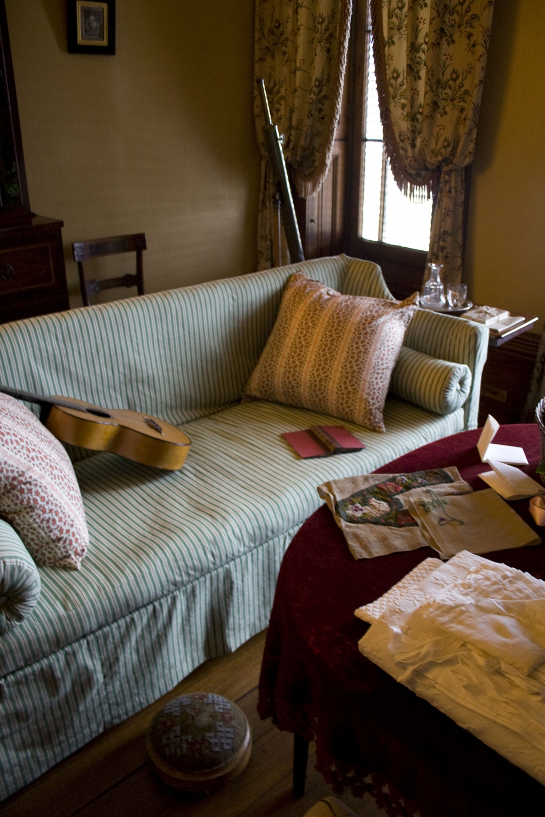 Fabric covered sofa and guitar in morning room at Elizabeth Bay House