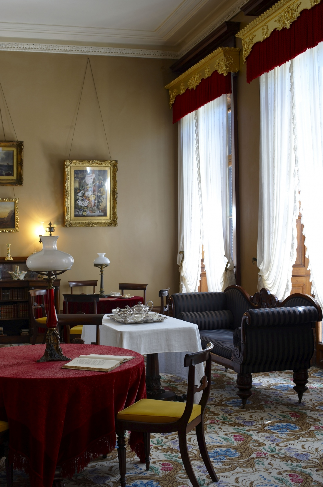 View of richly furnished room with tables, sofas, table lamps, gilt framed pictures, tall sunlit windows and curtains.