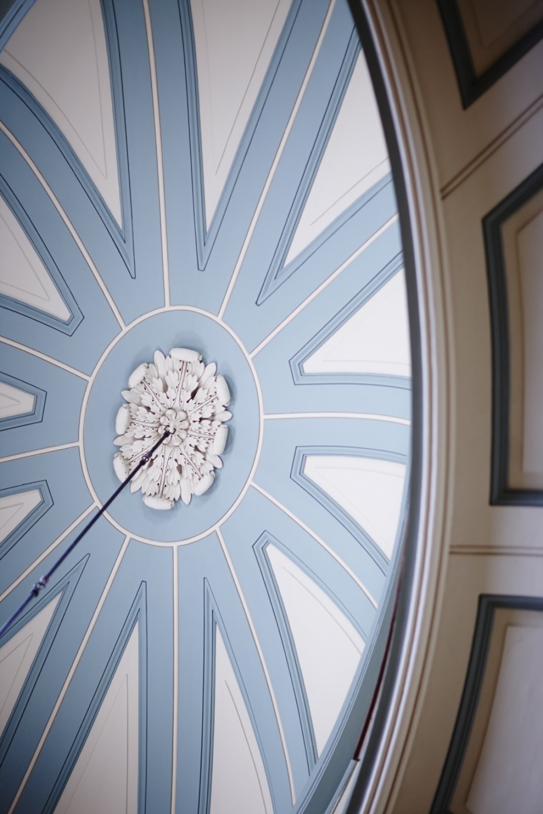 Looking up towards blue and white patterned dome with ceiling rose in centre.