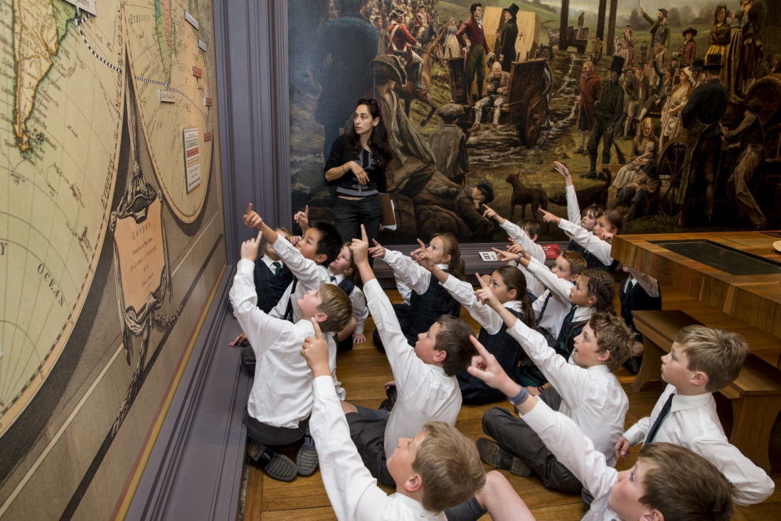 Group of seated students pointing at wall.