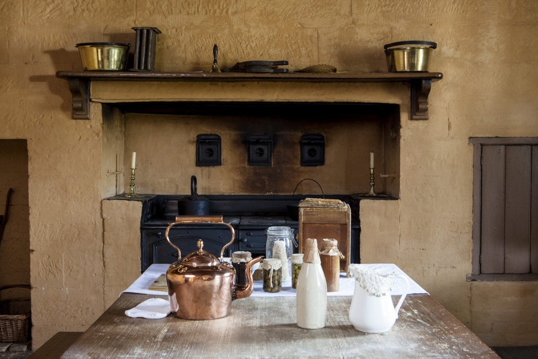 Interior of period kitchen with implements on table and fireplace in background.