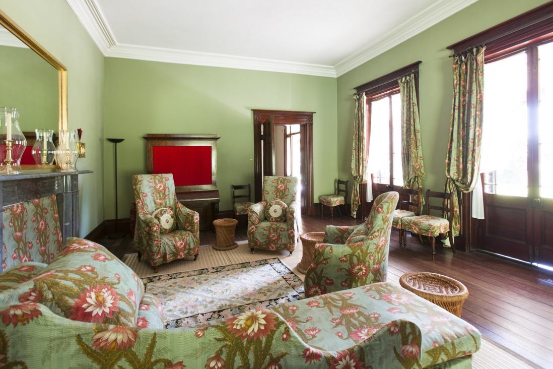 Interior of green sitting room with furniture.