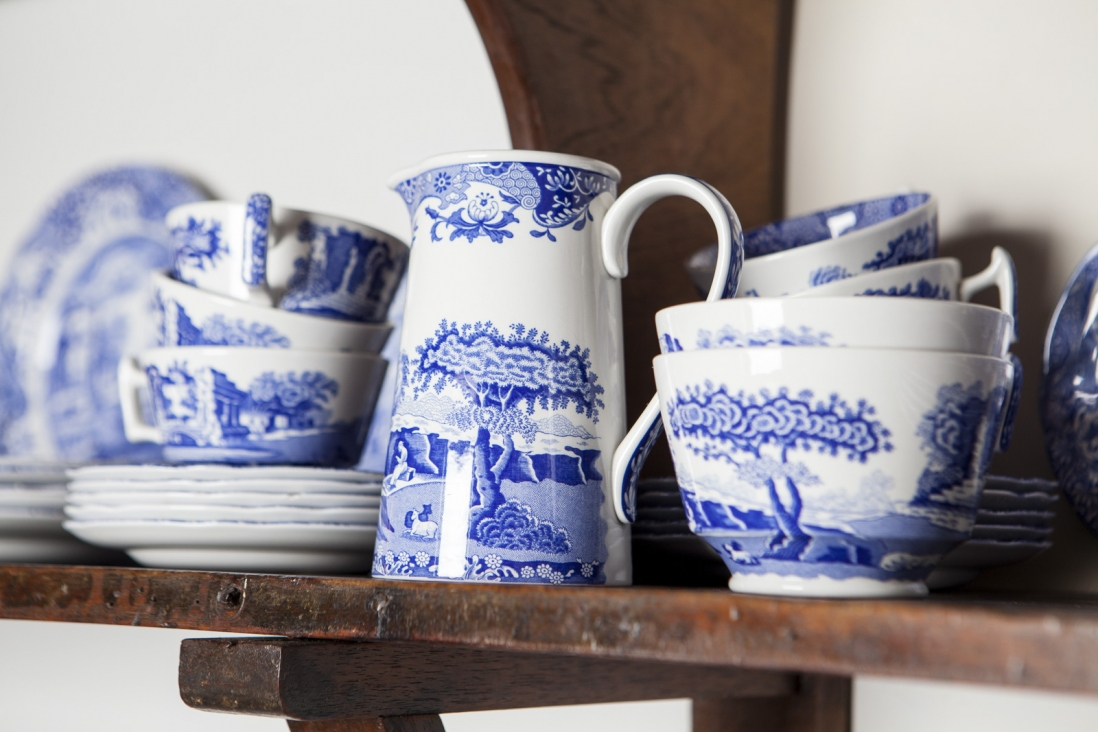 Closeup of blue and white bowls and jug on wooden shelf.
