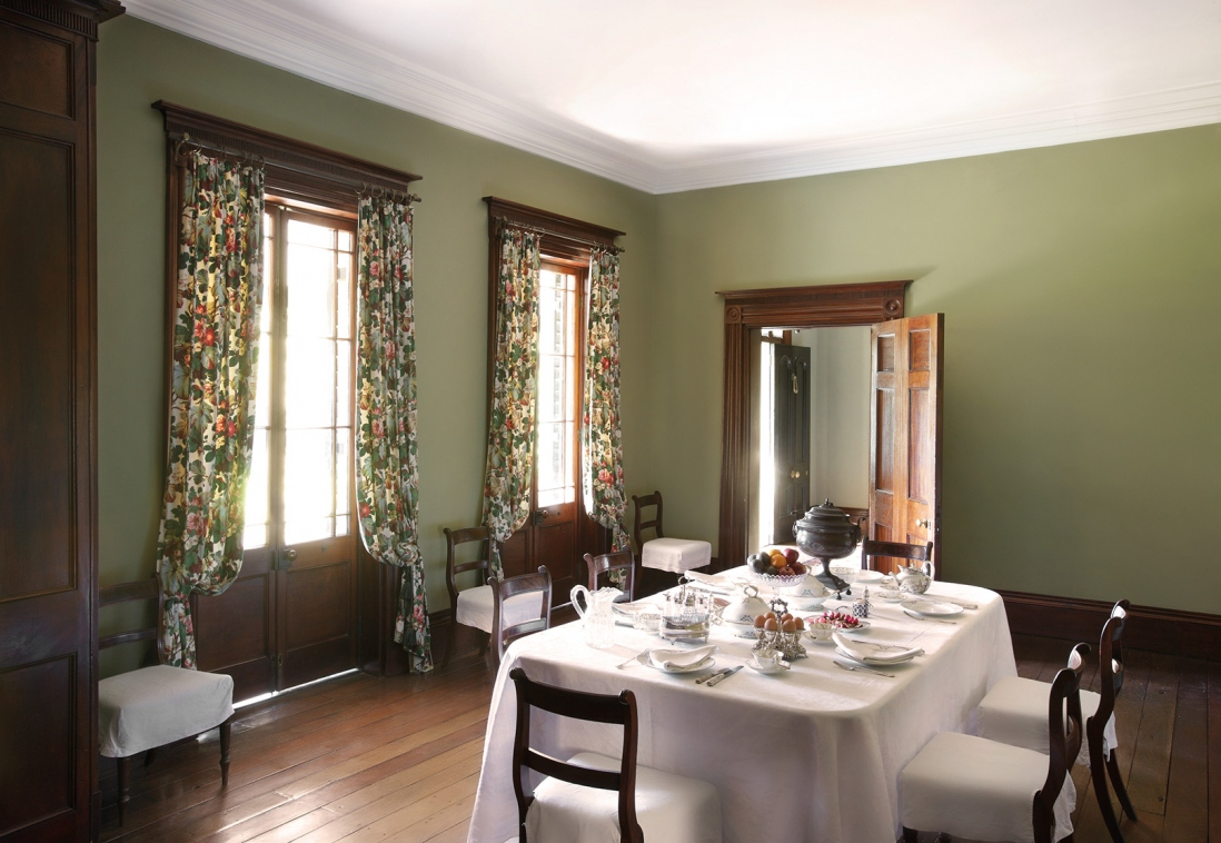 Interior of room with dining table against backdrop of draped windows and open door.