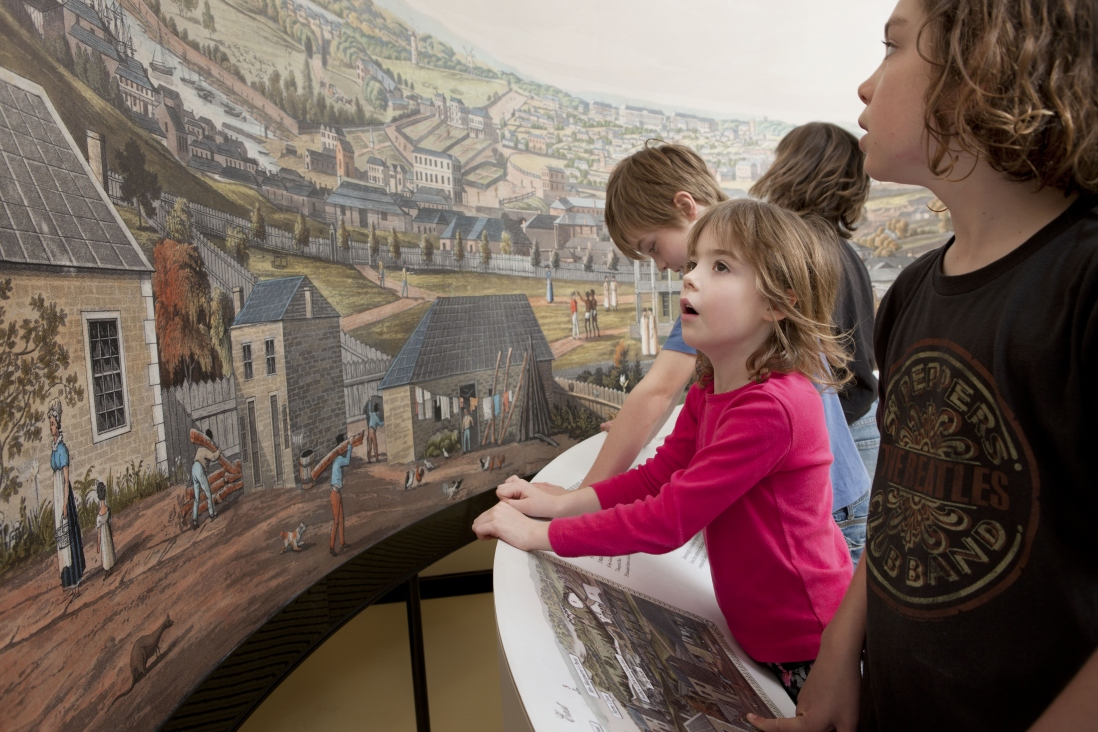 Young girl wearing red jumper, leaning against display panel, views large photographic reproduction of colonial painting