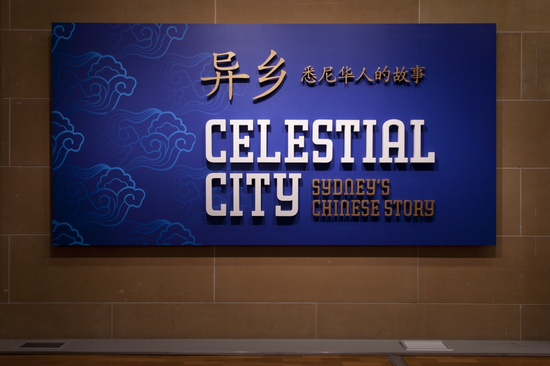 This is a photograph of a blue panel on a sandstone wall. On the panel in white lettering are the words Celestial City with gold lettering for the words Sydney's Chinese Story and the Chinese language translation