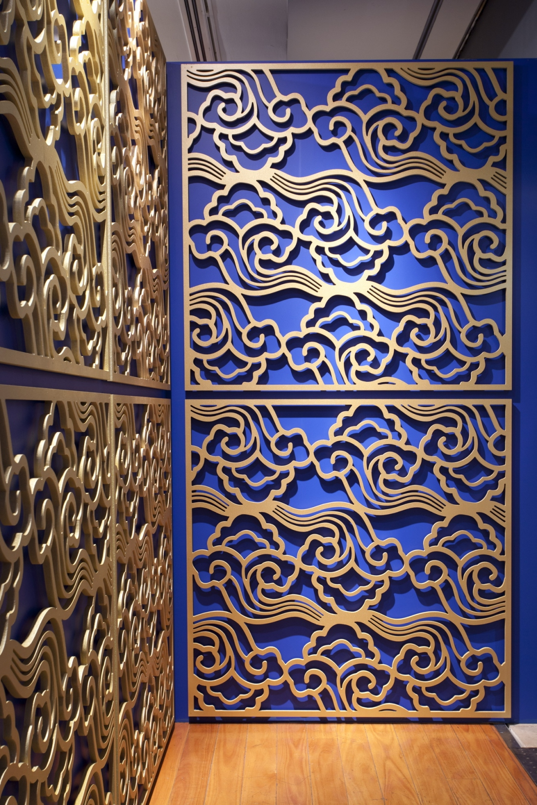 This is a photograph of gold painted cut-out panels featuring a cloud pattern on a blue wall