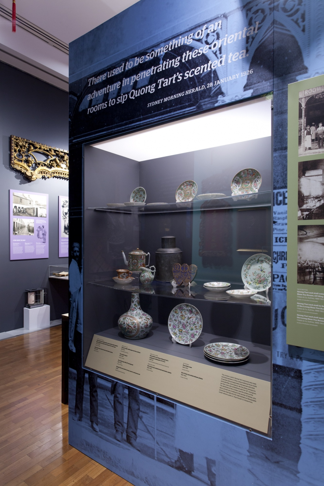 This is a photograph of a showcase featuring ceramics from the Quong Tart tearooms