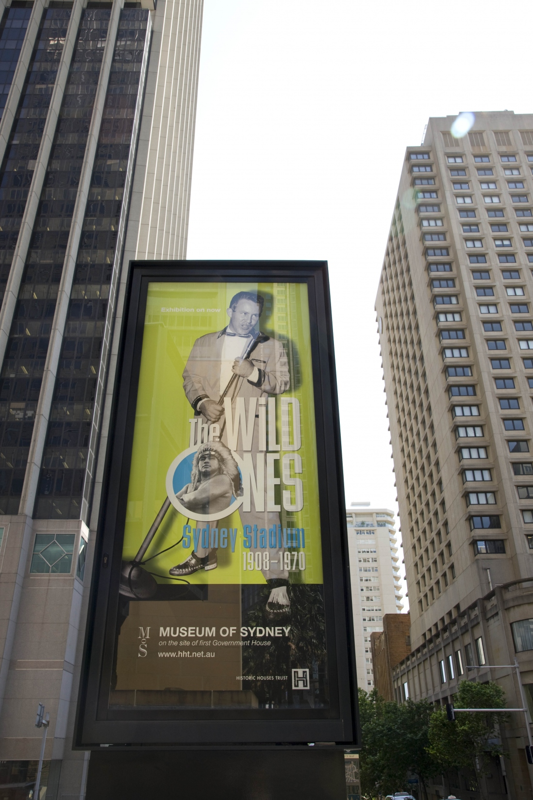 Large sign outside museum reads Wild Ones with a picture of a man holding a microphone.