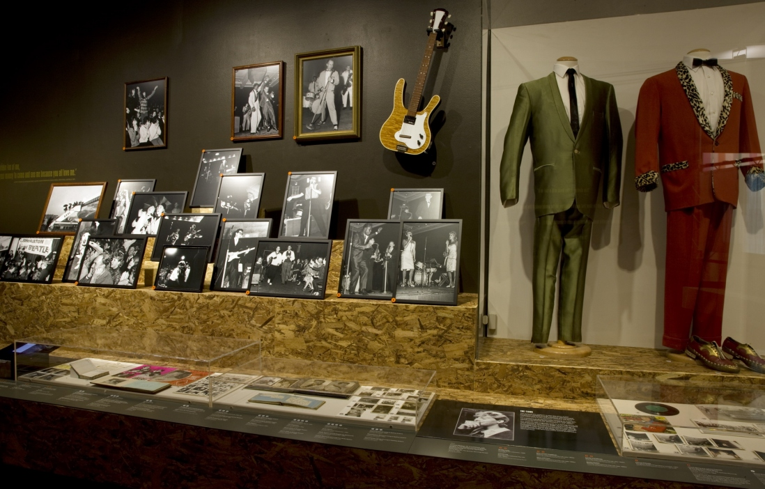 Interior view of exhibition space showing guitars, framed photographs and suits.