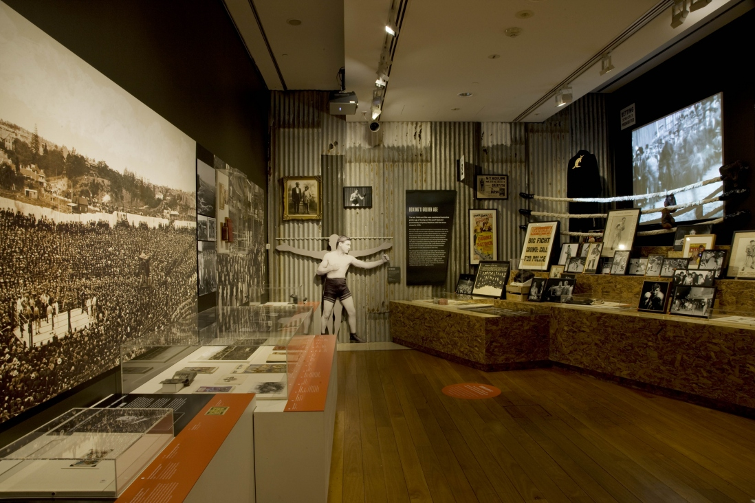 Exhibition interior showing display cases and pictures on the walls.