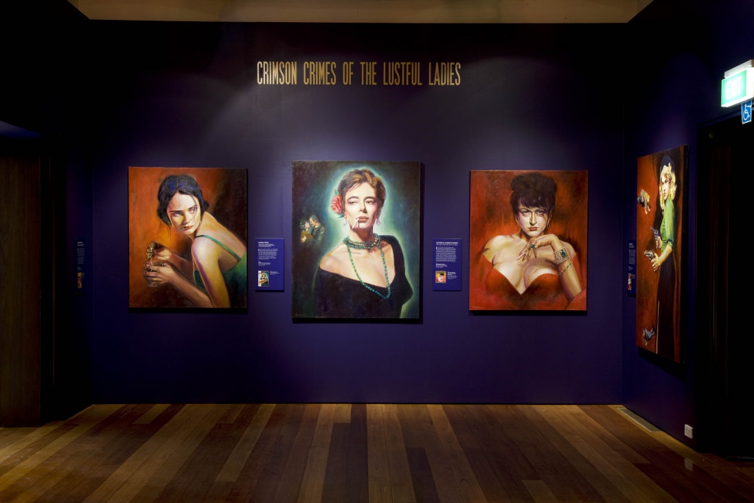 Interior of exhibition space showing colourful paintings of women on dark purple wall.
