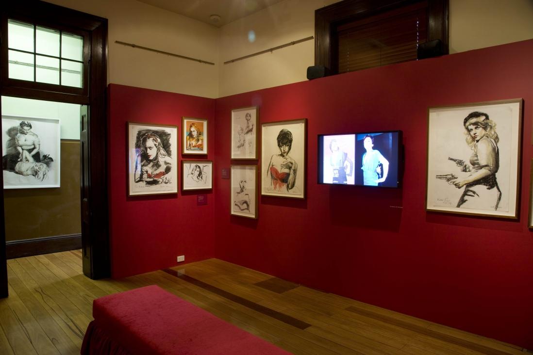 Exhibition interior showing drawings, posters and a screen on red walls.