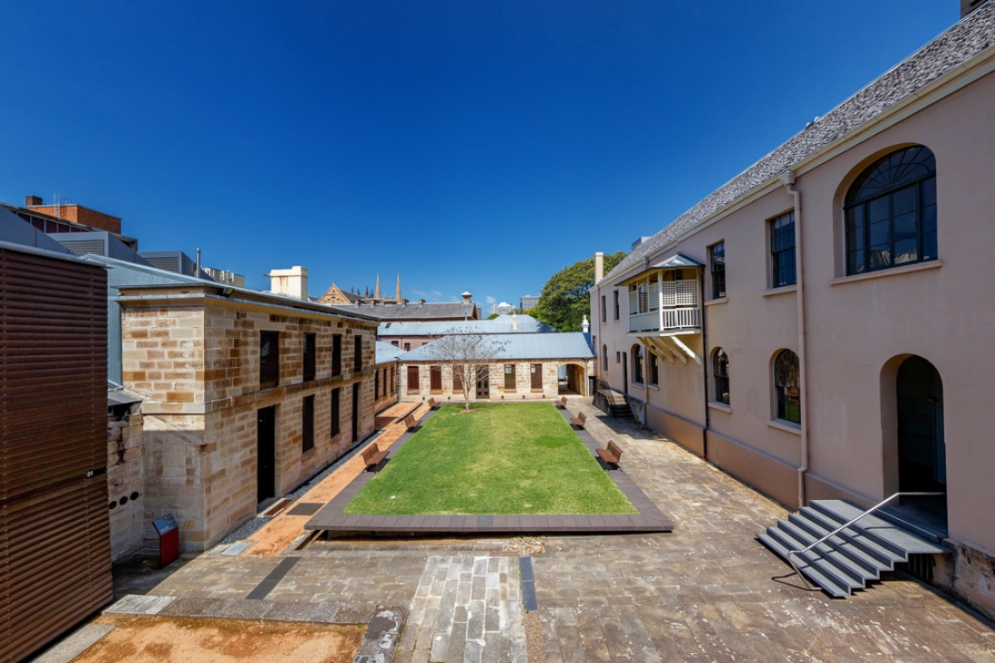 Courtyard area with lawn surrounded by sandstone paving and walled in by three building wings.
