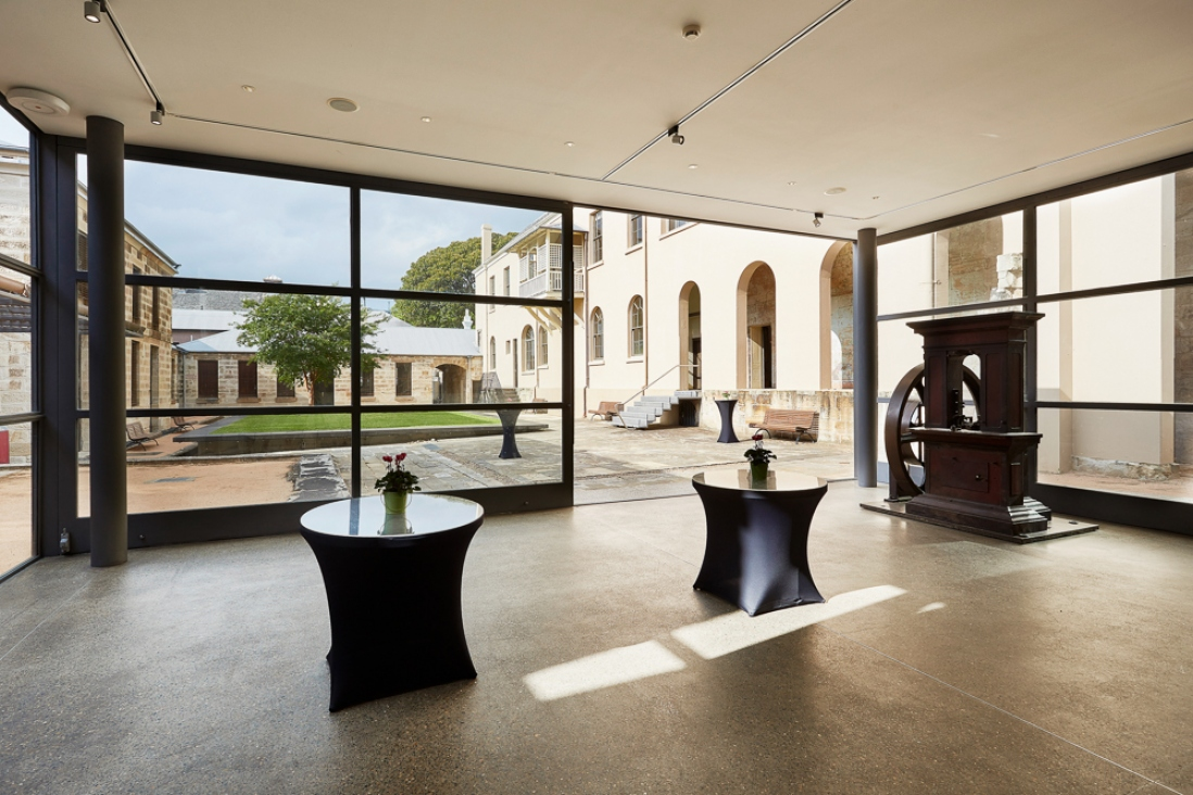 Tables in glass-walled room with courtyard behind.