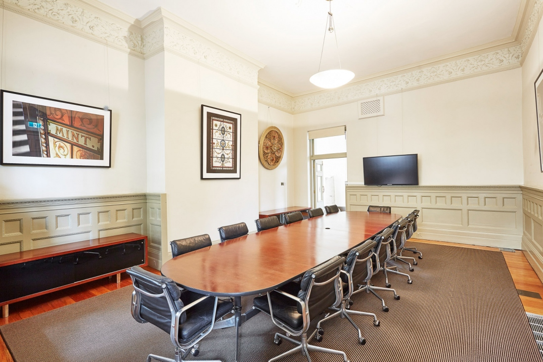 Boardroom table with seating in high-ceilinged room.