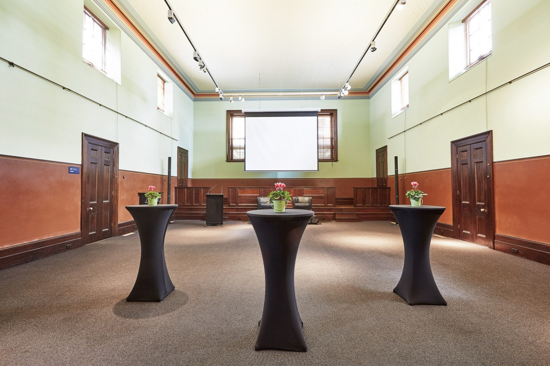 Cocktail tables set up in old style courtroom setting.