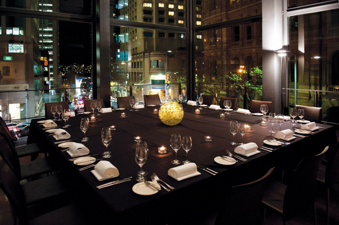 Glass-walled room with table set for dinner.