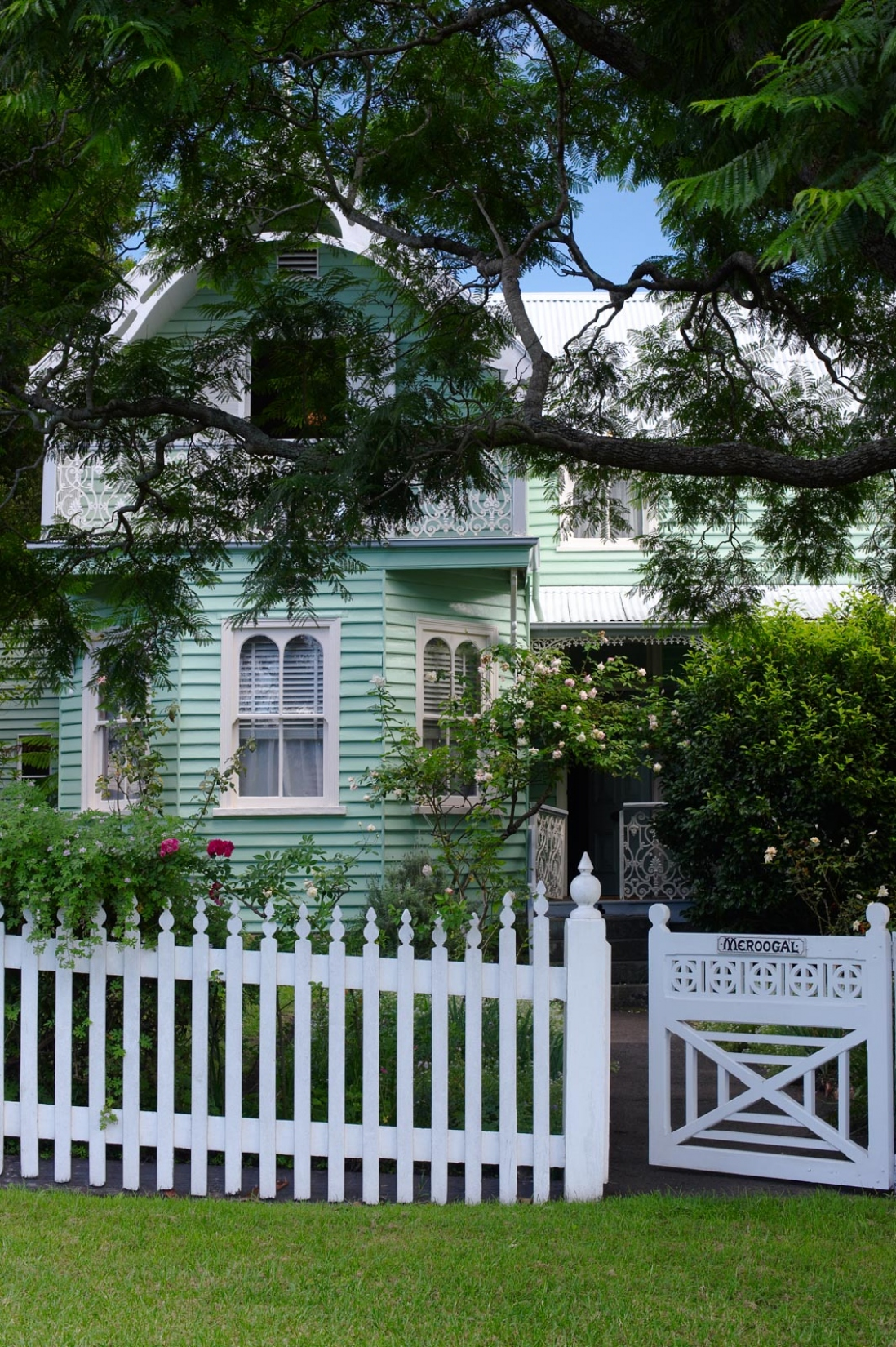 Exterior of wooden house with white picket fence and gate in foreground.