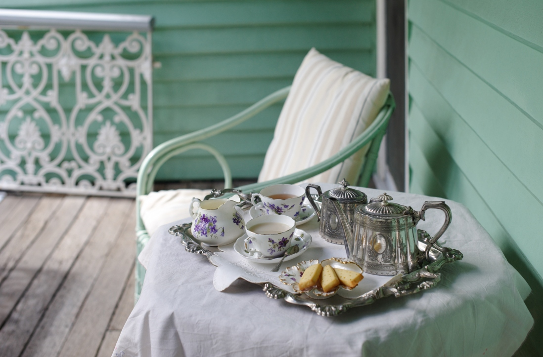 Wicker chair and table set for tea on small verandah of wooden house.