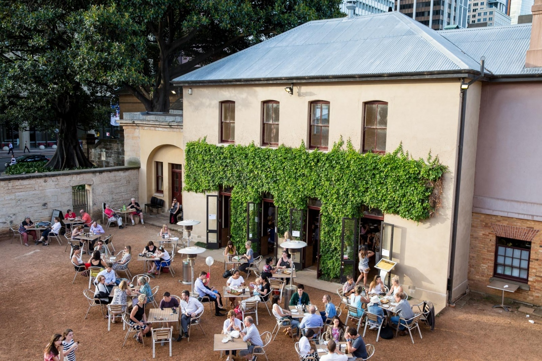 People seated at outdoor tables in front of building with ivy.