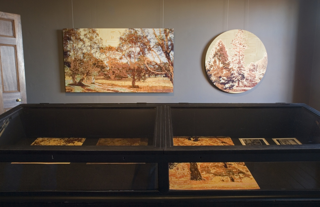 Two images hang on a wall above an old fashioned museum display case containing works on paper.