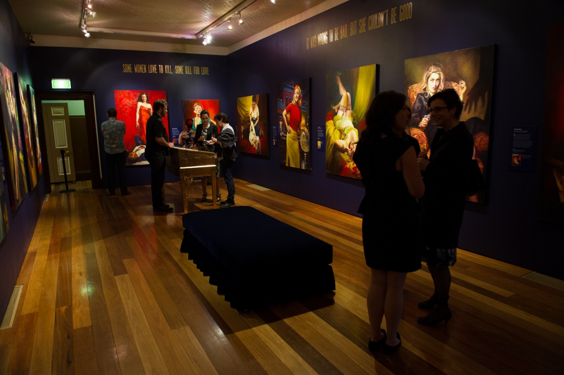 People milling around the main exhibition space during the opening of the exhibition. The room appears dimly lit with the paintings juming out.