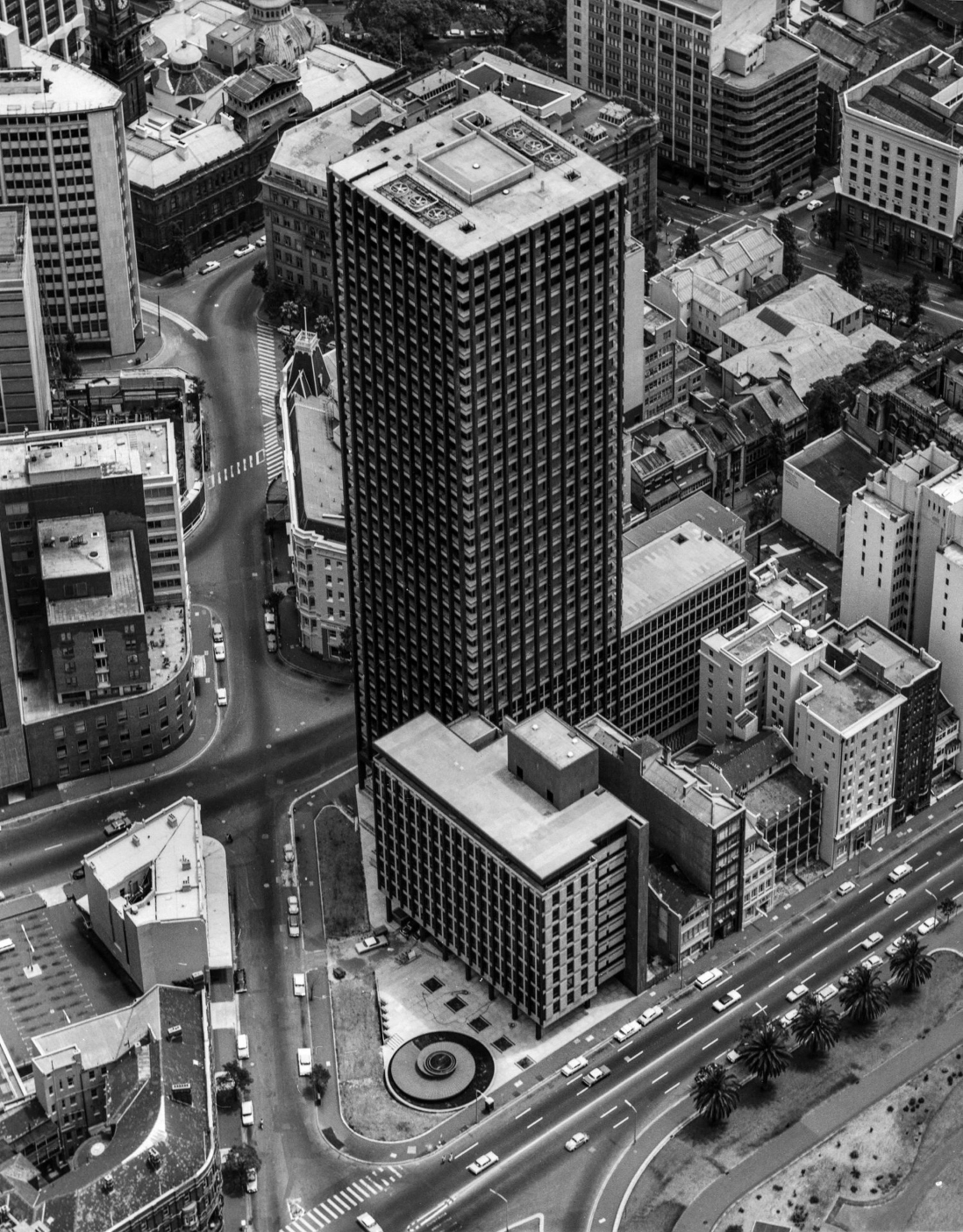 B&W image showing an aerial view of a skyscraper surrounded by smaller buildings on a street corner.