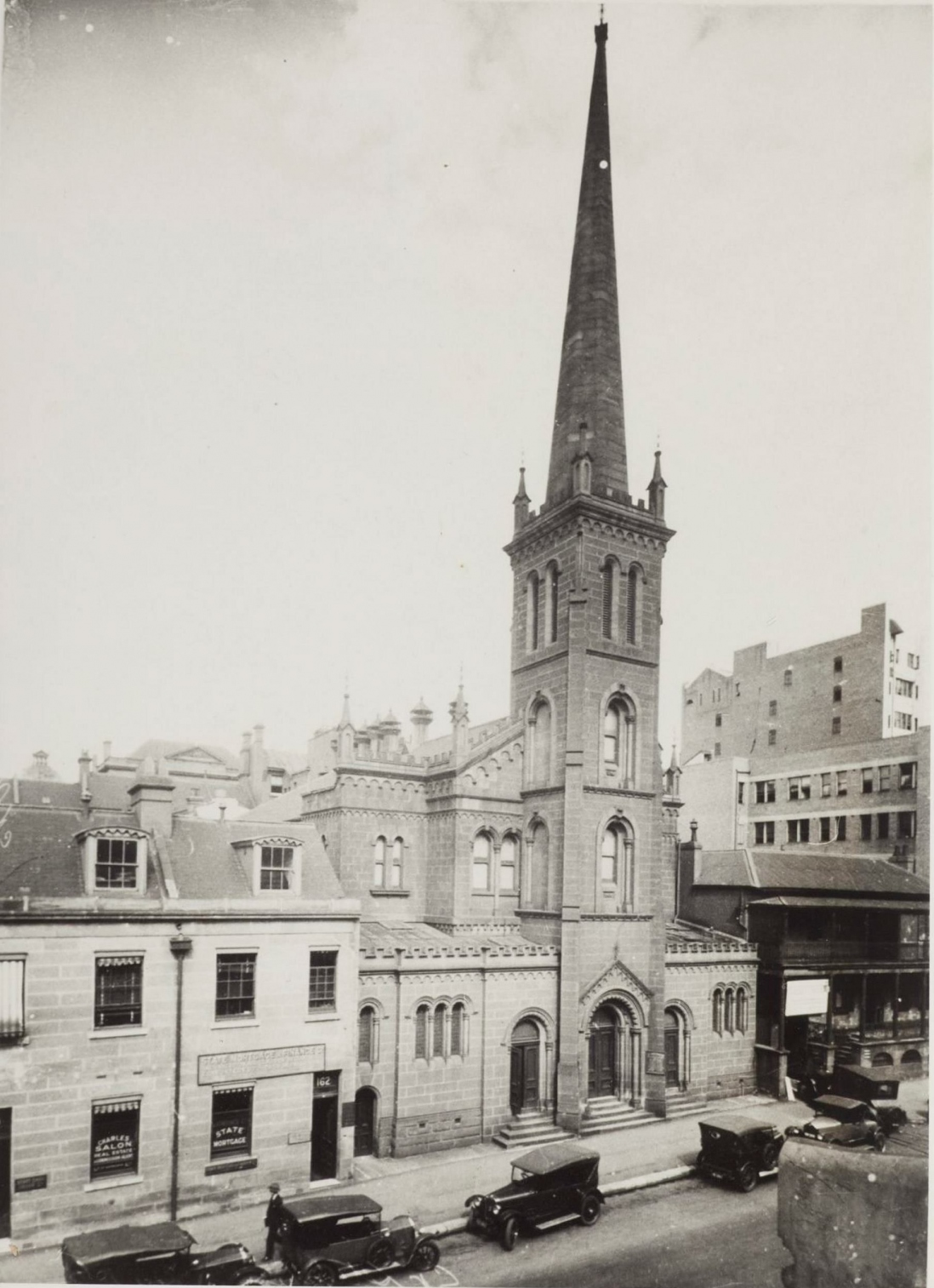 B&W image of a church with steeple, several vehicles parked on the street in front.
